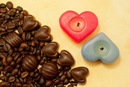 Two heart shaped candles and candies on grungy paper photo