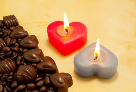 Two burning heart shaped candles and candies on a grungy background photo