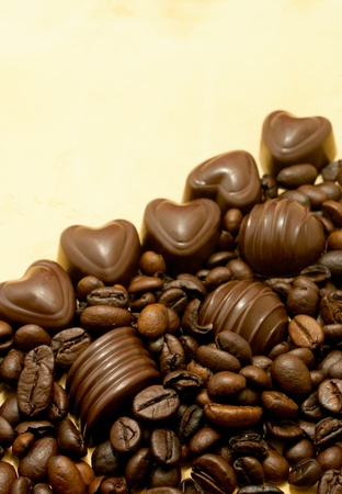 Heart shaped chocolate candies and coffee beans on grungy paper photo