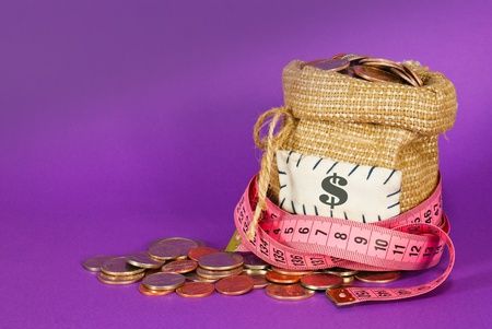 Sack full of coins over purple background photo