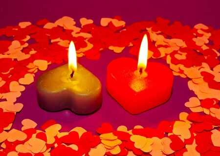 Two burning heart shaped candles over purple background