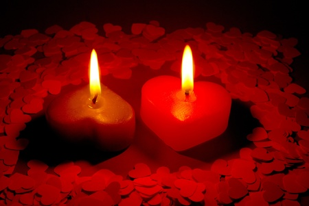 Two burning heart shaped candle on a red table photo