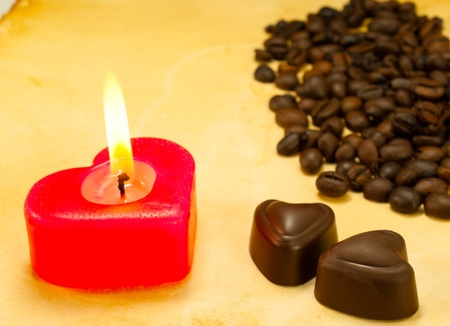 Burning candle, two heart shaped candies and cofee beans on grungy paper photo
