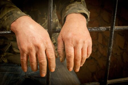 Man hands behind the bars against brick wall Stock Photo - 12520551