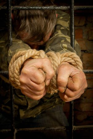 Man with hands tied with rope behind the bars photo