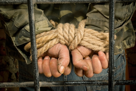 captivity: Man with hands tied up with rope behind the bars