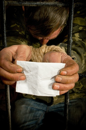 Man with hands tied up with rope behind the bars photo