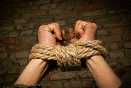 Hands of man tied up with rope against brick wall photo