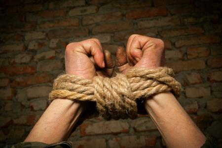 gefesselt: Hands of Mann mit einem Seil gegen Mauer gebunden