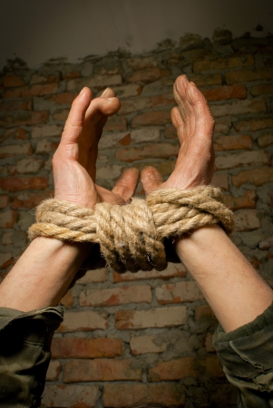 Hands tied up with rope against brick wall Stock Photo - 12520549