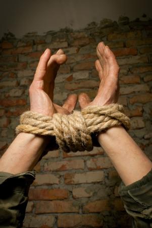 atados: Las manos atadas con una cuerda contra la pared de ladrillo
