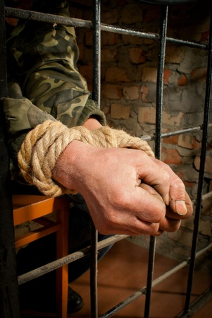 Hands of man tied up with rope behind the bars photo
