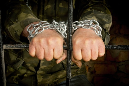 sentenced: Man with hands tied up with chain behind the bars