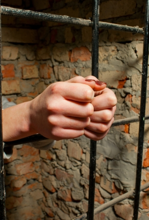 Woman hands behind the bars against brick wall Stock Photo - 12520841