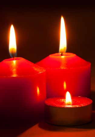 Three burning candles over red background