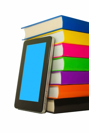 Stack of colorful books and tablet PC over white background photo