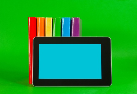 Row of colorful books and tablet PC over green background photo