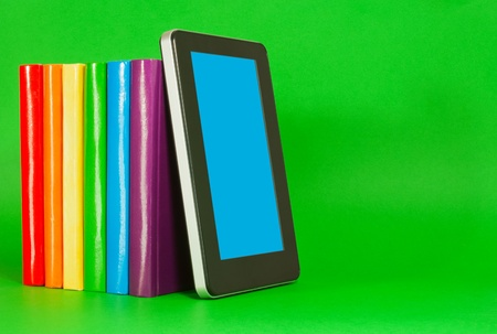 digitized: Row of colorful books and tablet PC over green background Stock Photo
