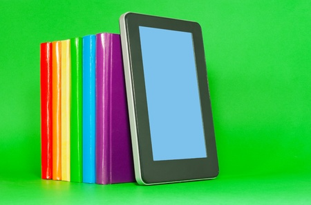 Row of colorful books and tablet PC over green background Stock Photo - 12831700