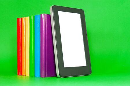 Row of colorful books and tablet PC over green background Stock Photo - 12831711