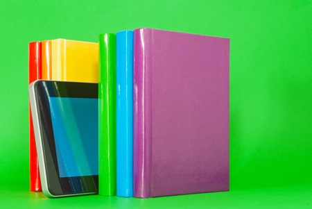 Row of colorful books and tablet PC over green background Stock Photo - 12831698