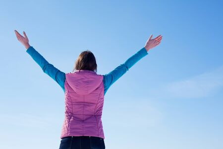Teen girl staying with raised hands against blue sky photo