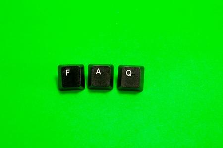 Three plastic keys with FAQ word over green background photo