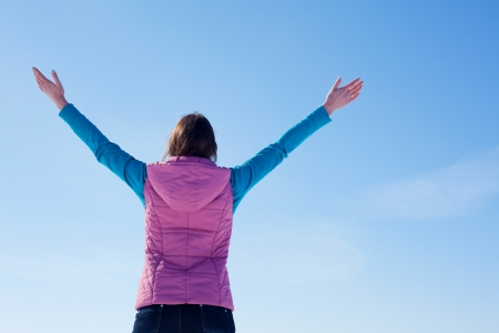 Teen girl staying with raised hands against blue sky Stock Photo - 12831791