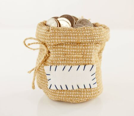 Sack full of coins against light background photo