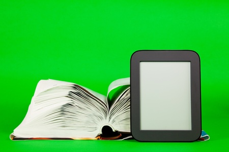 Open book and e-book reader against green background Stock Photo