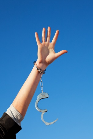 Handcuffed womans hand against blue sky photo