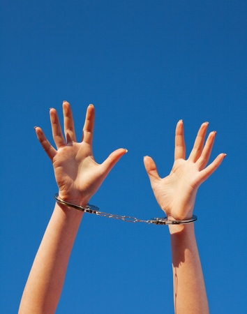 Handcuffed womans hands against blue sky photo