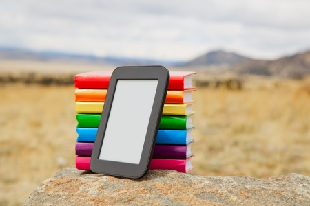 stilus: Stack of printed books with electronic book reader lying on the stone Stock Photo