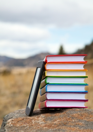 Stack of printed books with electronic book reader lying on the stone Stock Photo - 14159597