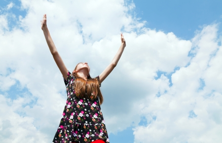 Teen girl with raised hands against blue cloudy sky Foto de archivo