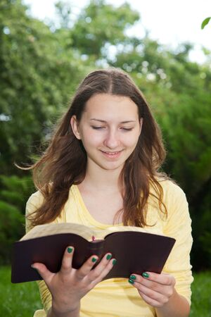 Teen girl reading book outdoors at summer time Stock Photo - 14157669