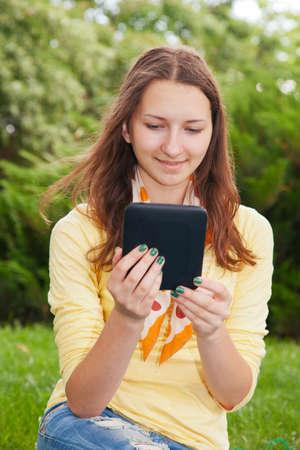 Teen girl reading electronic book outdoors