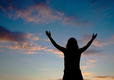 manos levantadas al cielo: Mujer quedarse con las manos levantadas en el momento de puesta de sol