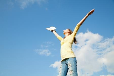 manos levantadas al cielo: Joven mujer quedarse con las manos levantadas contra el cielo azul Foto de archivo