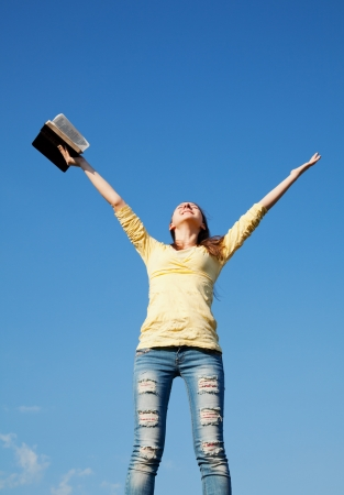 Young woman staying with raised hands against blue sky Stock Photo - 14157682