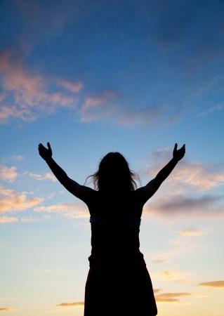 reaching hands: Vrouw verblijft met opgeheven handen bij de zonsondergang tijd