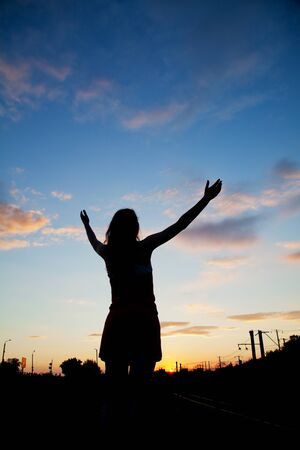 Woman staying with raised hands at the sunset time Stock Photo - 14157688