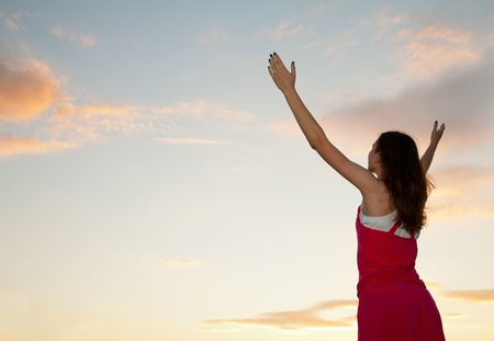 with raised: Woman staying with raised hands at the sunset time