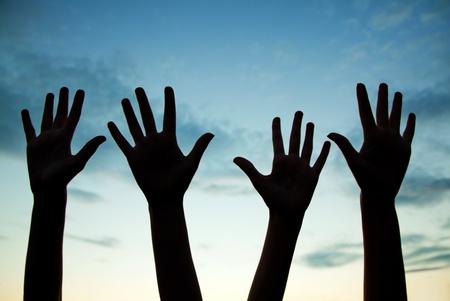 manos levantadas al cielo: Cuatro manos levantadas contra el cielo crepuscular Foto de archivo
