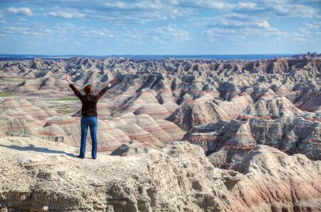 Woman with raised hands against terrain landscape photo