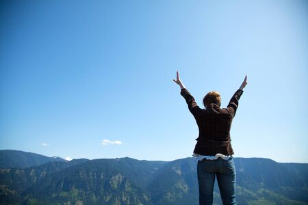 Woman with raised hands against blue sky photo