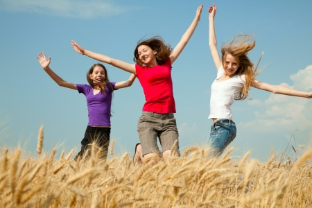 Teen girls jumping at a wheat field in a sunny day photo