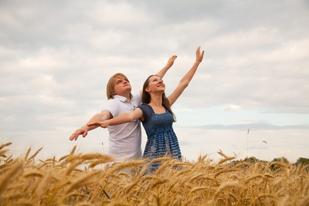 Couple staying with raised at wheat field hands at sunset time photo