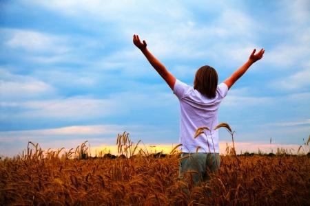 日没時に小麦のフィールドの手で提起された若い男と一緒に暮らす 写真素材