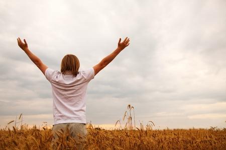 manos levantadas al cielo: Hombre joven en casa de plantearse en las manos del campo de trigo en la puesta del sol Foto de archivo
